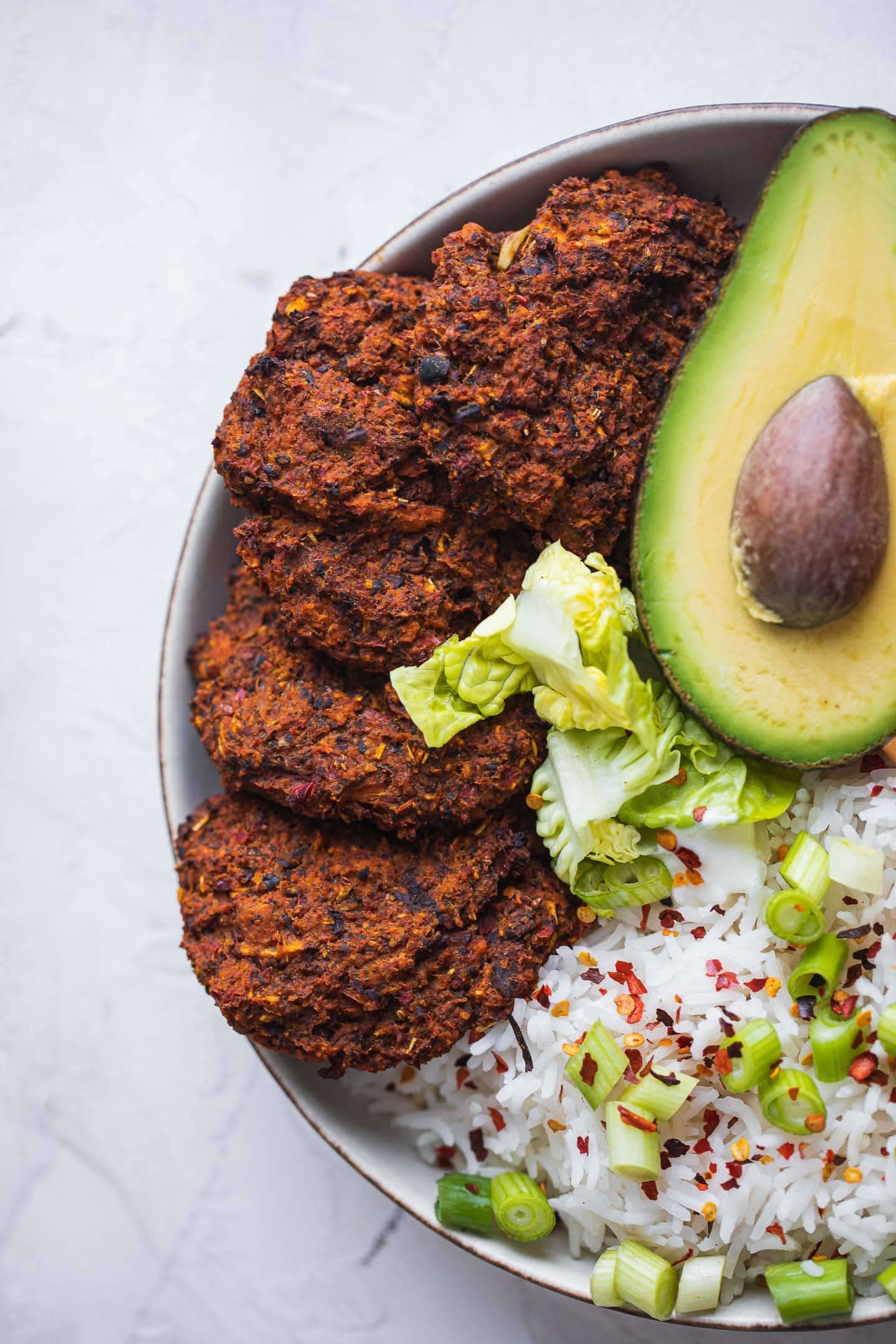 Vegan black bean burgers in a nourish bowl with rice and avocado