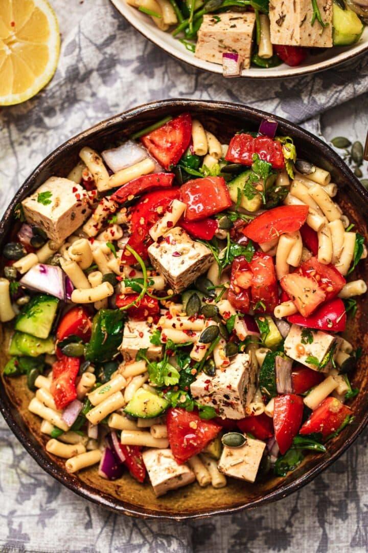 Bowl of vegan pasta salad with tofu feta and vegetables