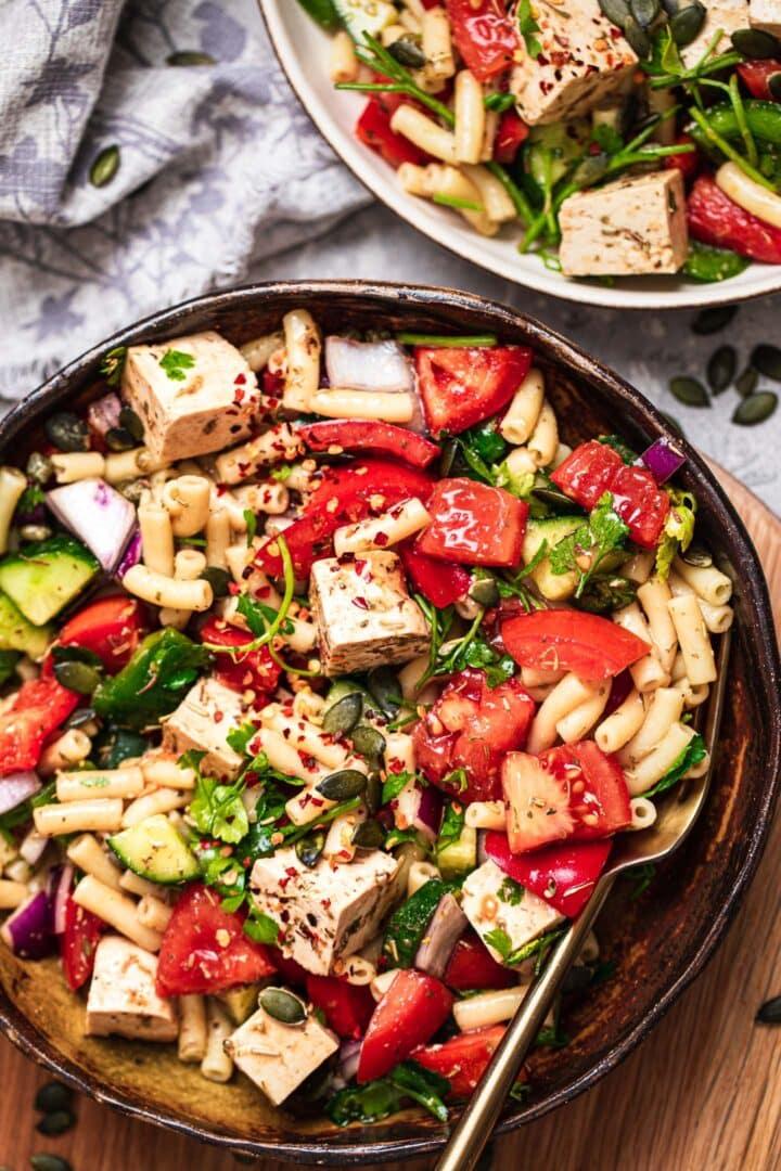 Bowl of vegan pasta with tofu feta and vegetables