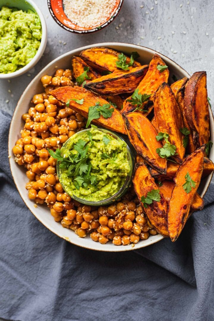Bowl with homemade sweet potato wedges, chickpeas and guacamole