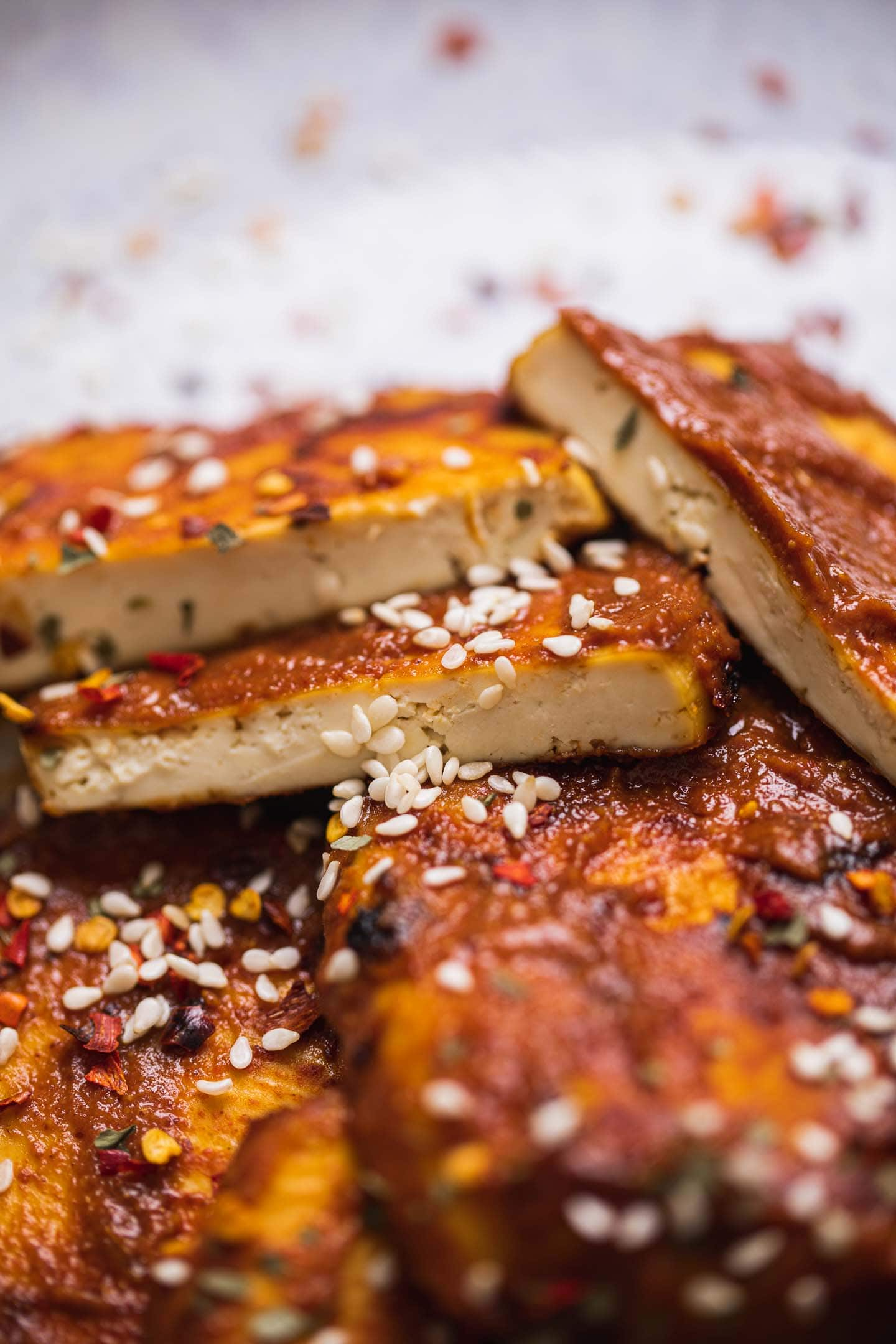 Closeup of baked tofu in a miso glaze and sesame seeds