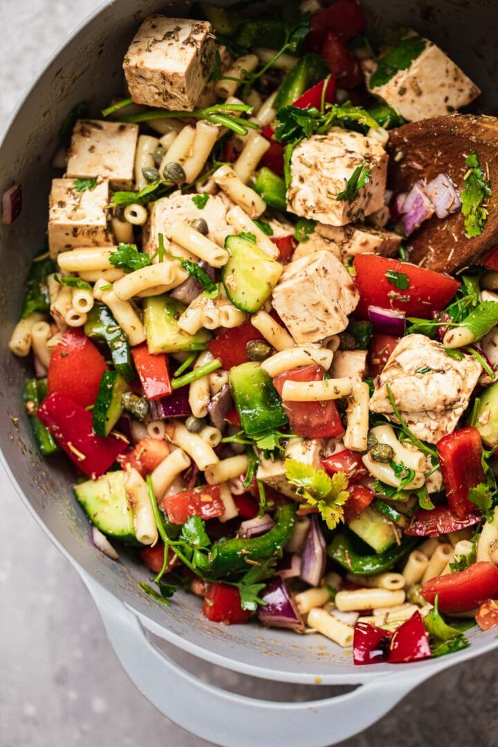 Pasta salad with tofu feta in a large mixing bowl