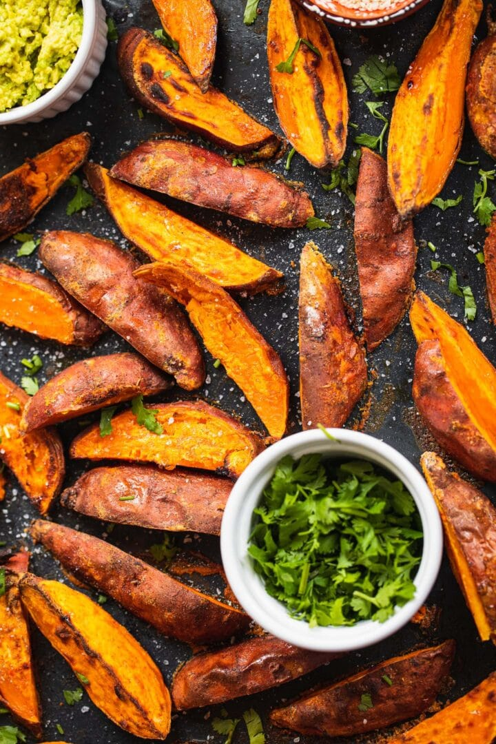 Sweet potato fries on a baking tray with guacamole