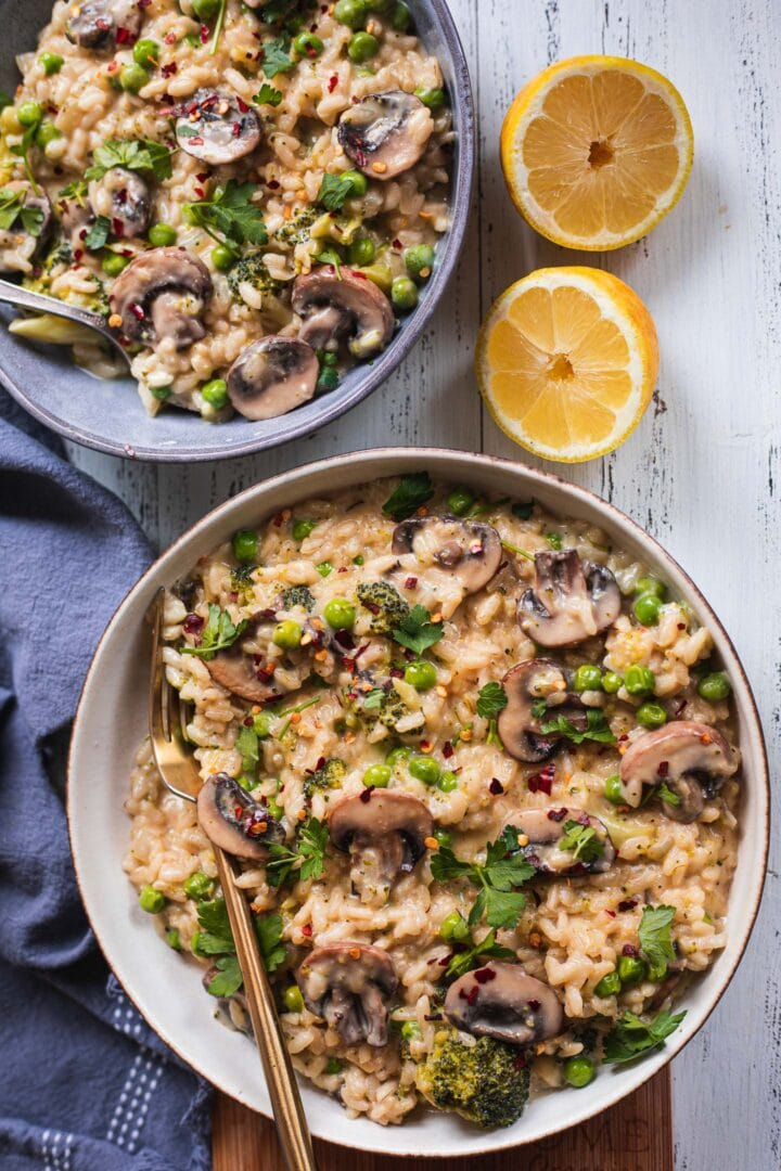 Two bowls of dairy-free risotto with mushrooms and broccoli