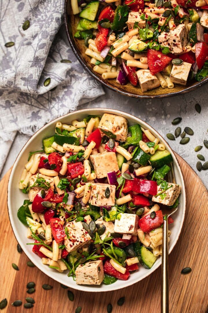 Two bowls of vegan pasta salad with vegetables and fresh herbs