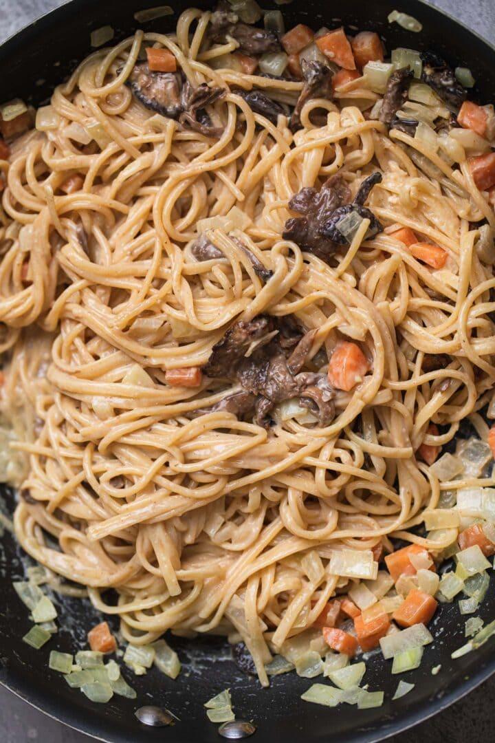 Vegan spaghetti in a frying pan with a carbonara sauce