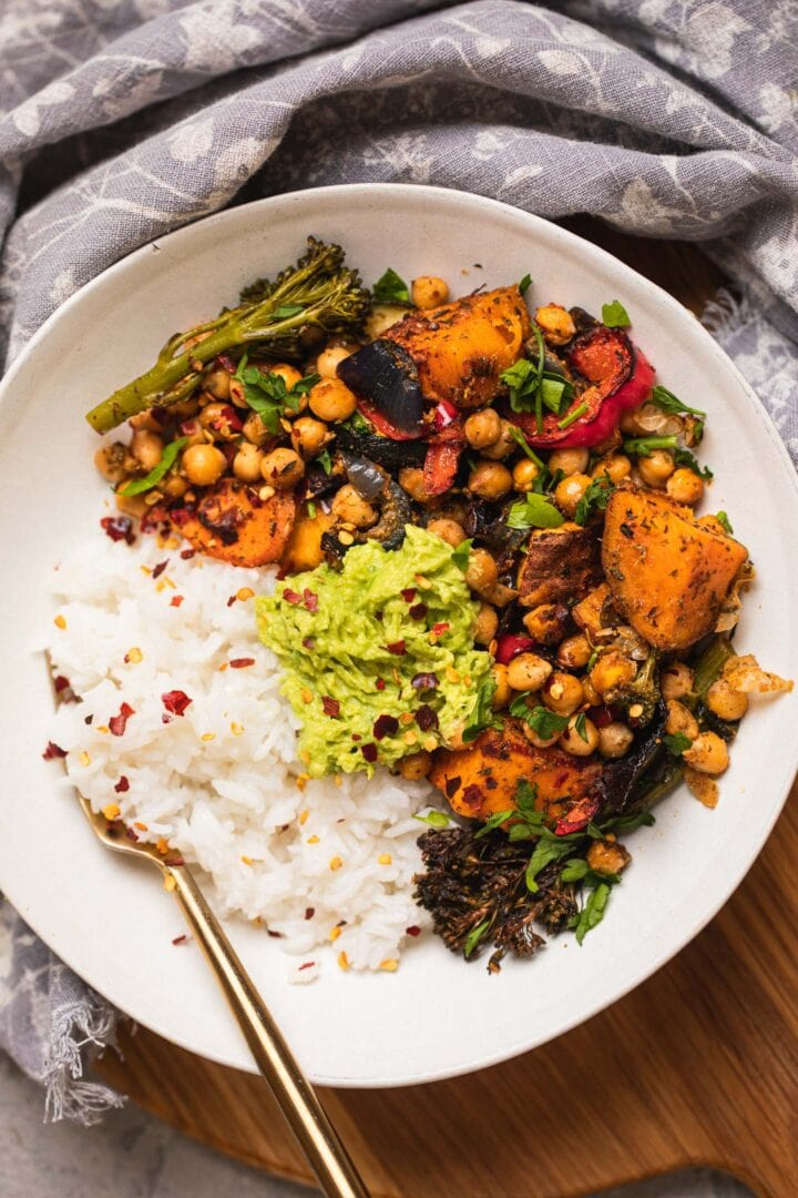 Bowl of roasted vegetables and chickpeas with rice and avocado