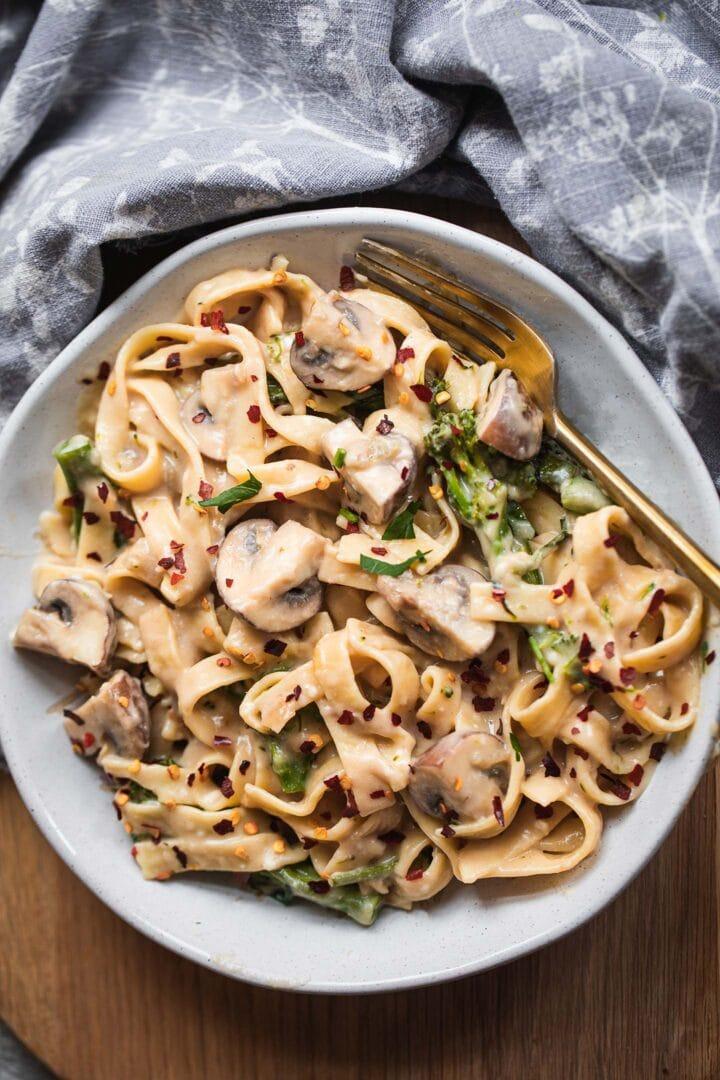Bowl of vegan pasta with broccoli and mushrooms