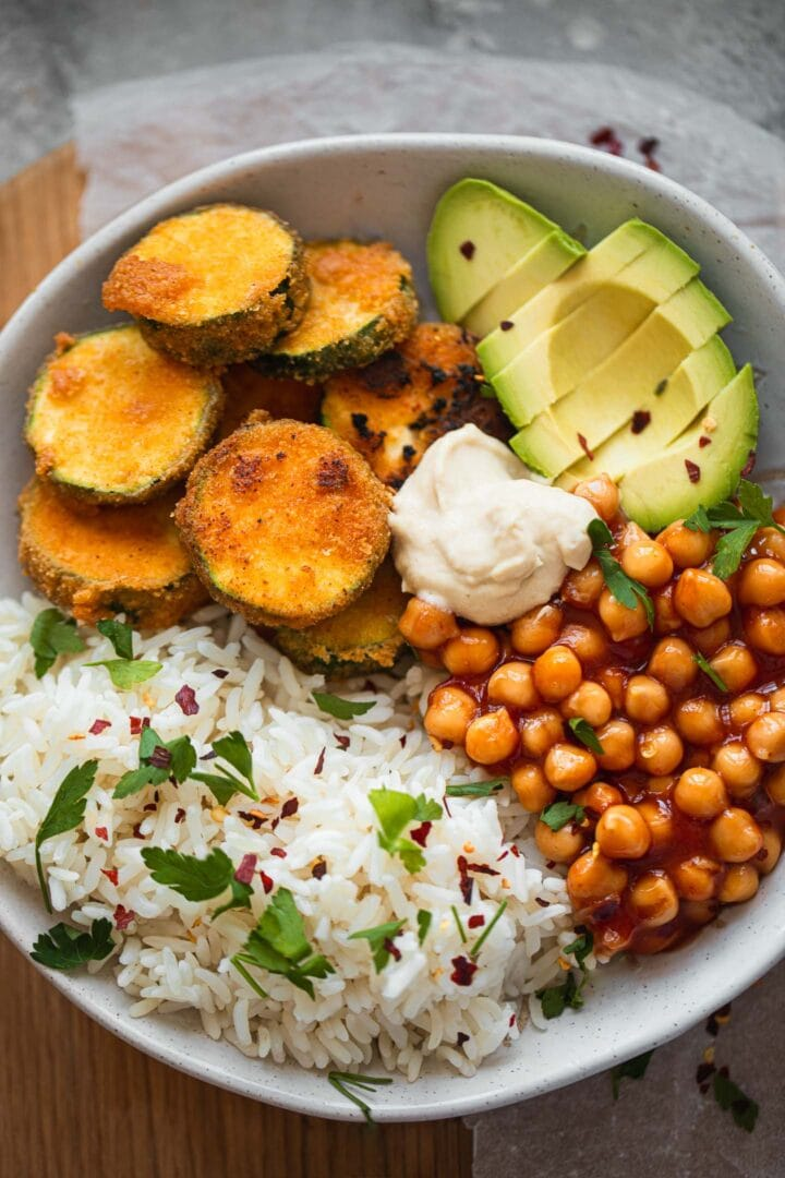 Bowl with fried zucchini, avocado, chickpeas and rice