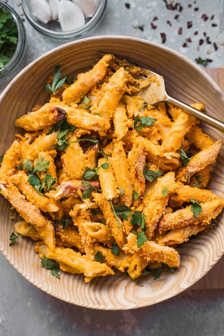 Cheesy vegan pasta in a bowl with fresh herbs and breadcrumbs