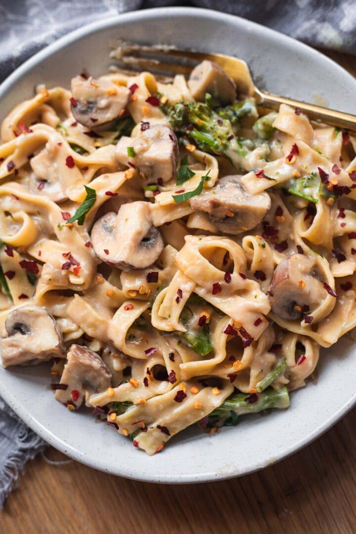Closeup of a pasta bowl with broccoli, mushrooms and a creamy sauce