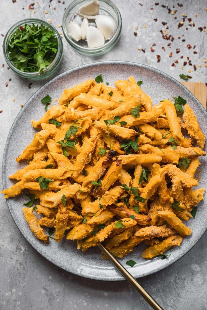 Dairy-free mac and cheese with breadcrumbs and fresh herbs on a plate