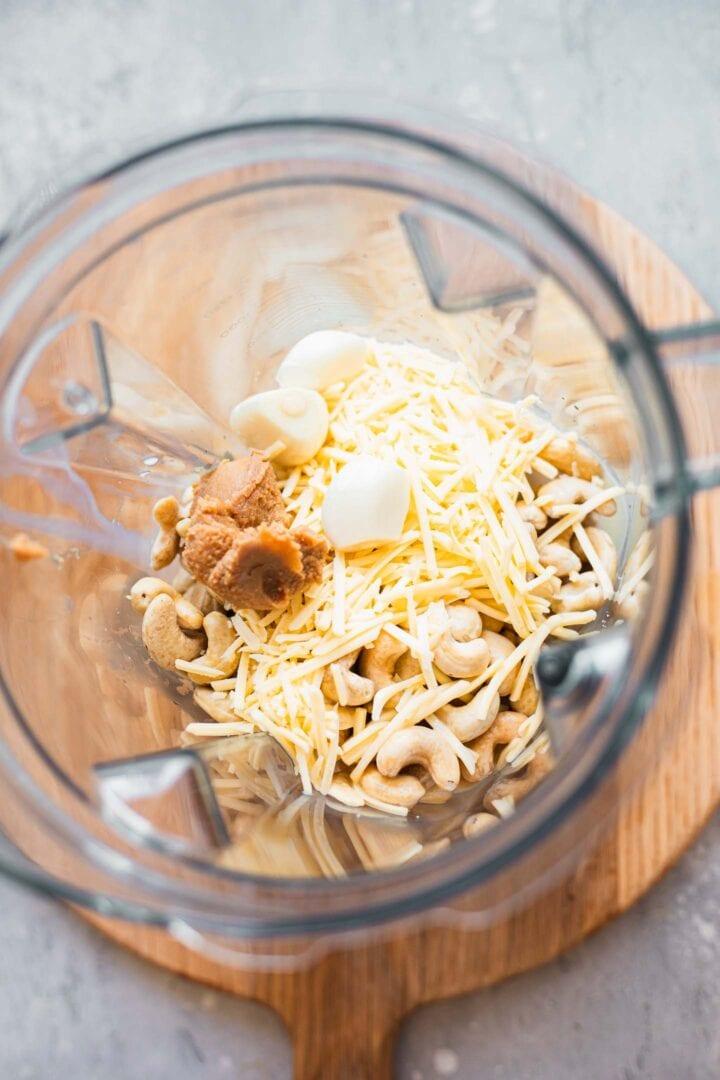 Ingredients for garlic cashew dip in a blender