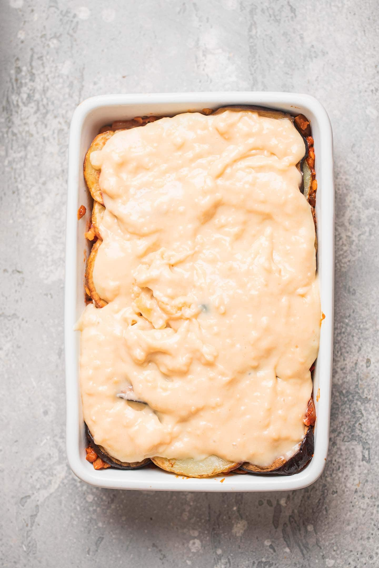 Lentil Moussaka with a dairy-free Bechamel sauce before baking