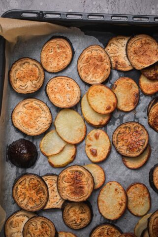 Roasted potatoes and aubergines on a baking tray