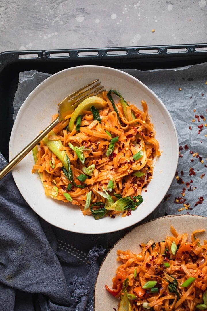 Two bowls of vegan noodles with a spicy sauce and a Pak Choi