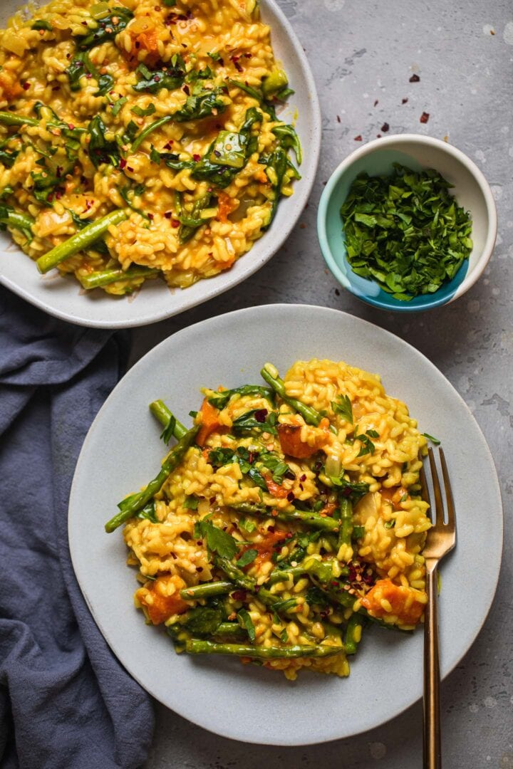 Two bowls of vegan risotto with butternut squash and asparagus