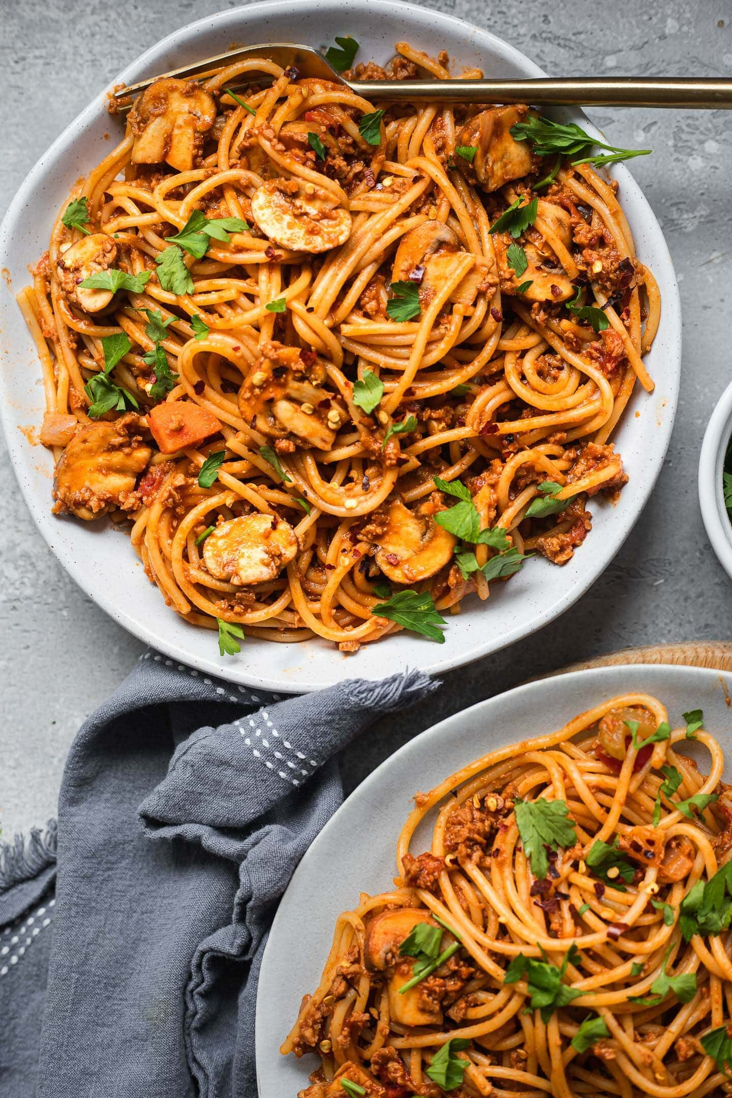 Two bowls of vegetarian spaghetti with a tomato pasta sauce