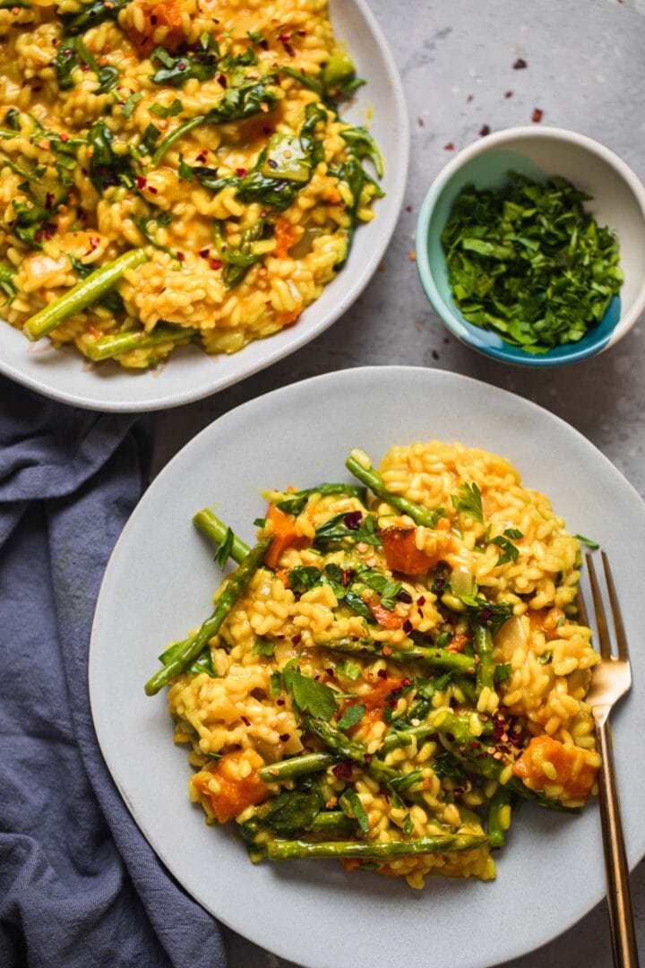 Two plates of butternut squash risotto with asparagus