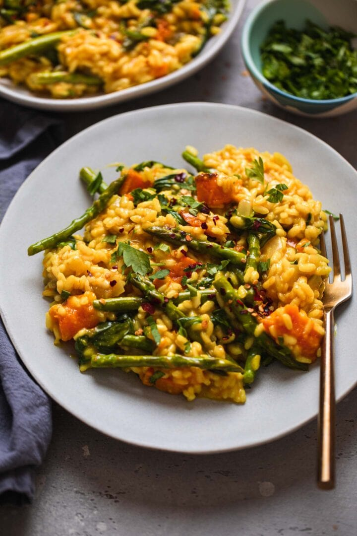 Two plates of vegan risotto with butternut squash and asparagus