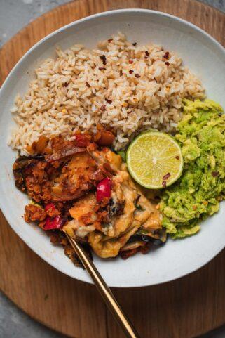 Wholegrain rice, vegan Moussaka and avocado in a bowl