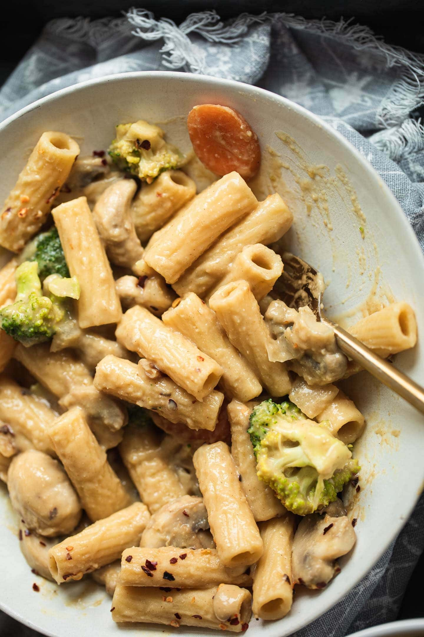 Bowl of pasta with mushrooms, broccoli and carrots