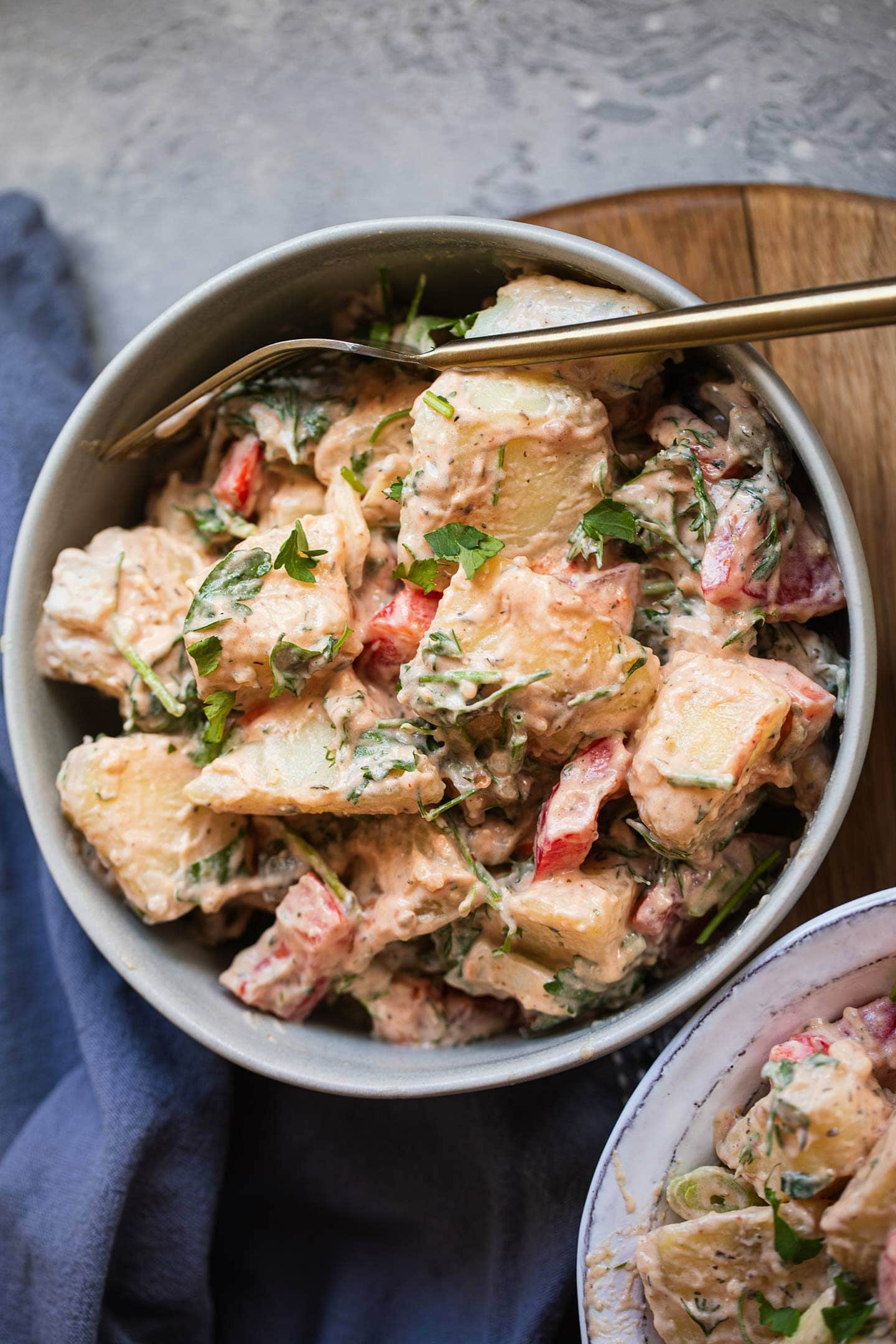Bowl of potato salad with vegetables and herbs