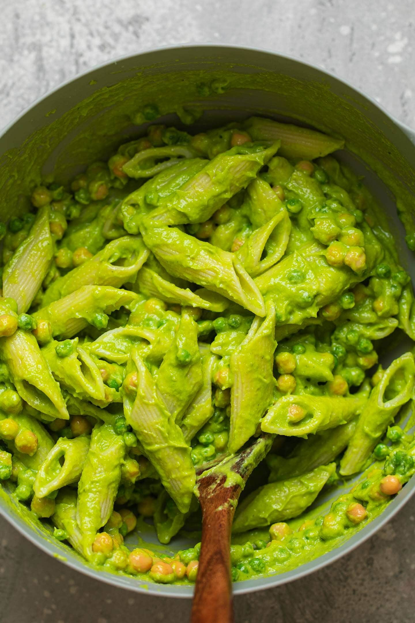 Pesto pasta in a mixing bowl with chickpeas