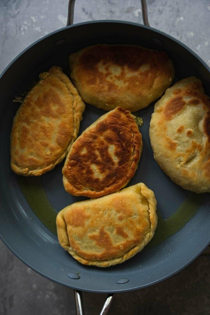 Piroshki being cooked in a frying pan
