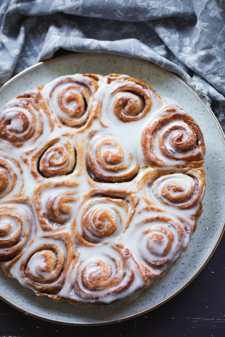 Plate with vegan cinnamon rolls and icing