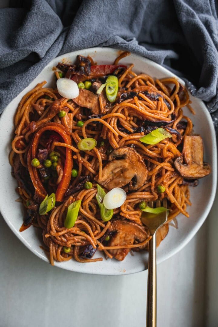 Bowl of vegan pasta with vegetables and spring onion