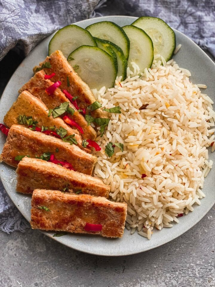 Bowl of crispy tofu with rice and cucumbers