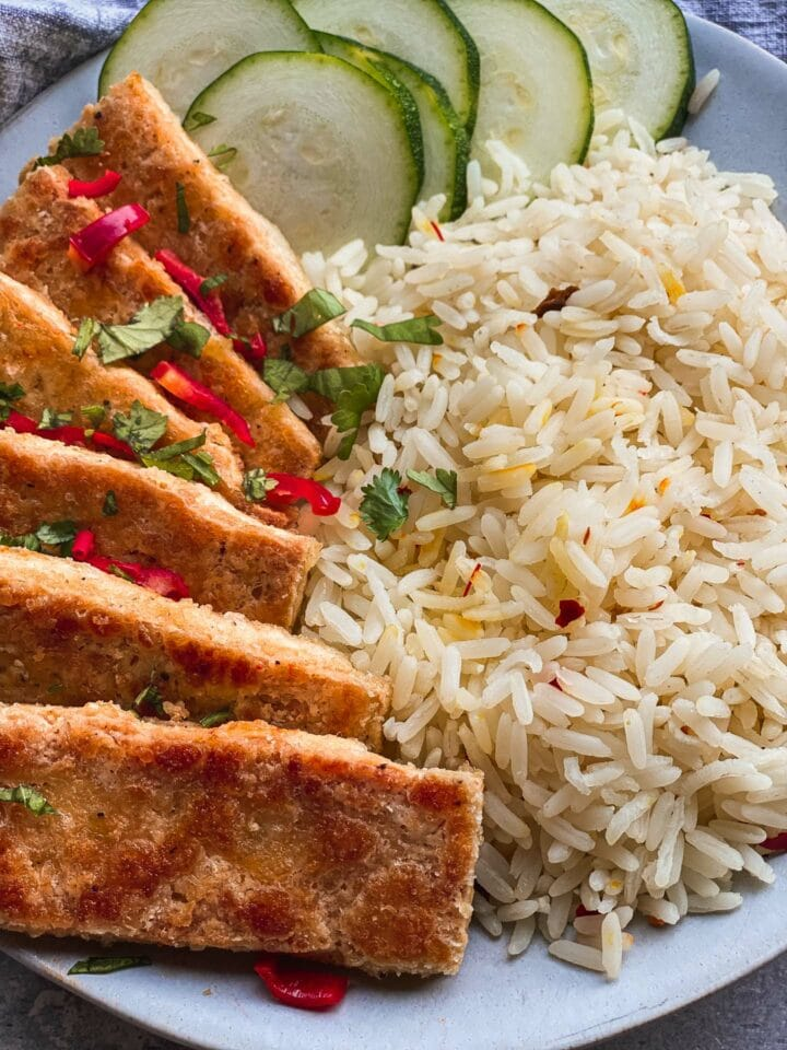 Closeup of salt and pepper tofu with rice and cucumber