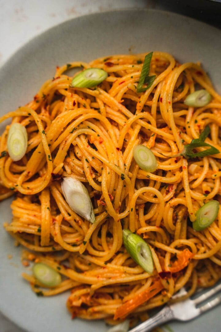 Spaghetti on a plate with peppers and scallions