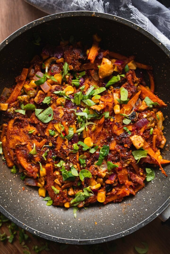 Sweet potato in a skillet with peas and sweetcorn