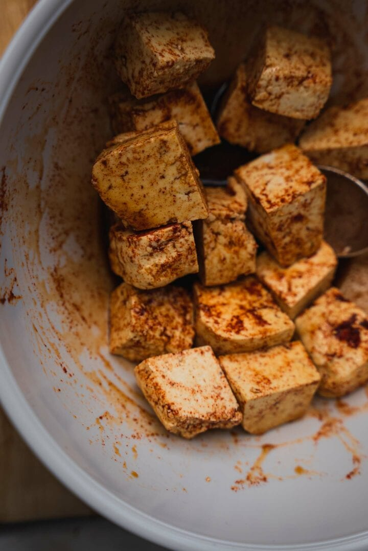 Tofu and spices in a mixing bowl