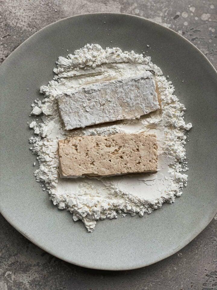 Tofu being coated in a cornstarch mixture