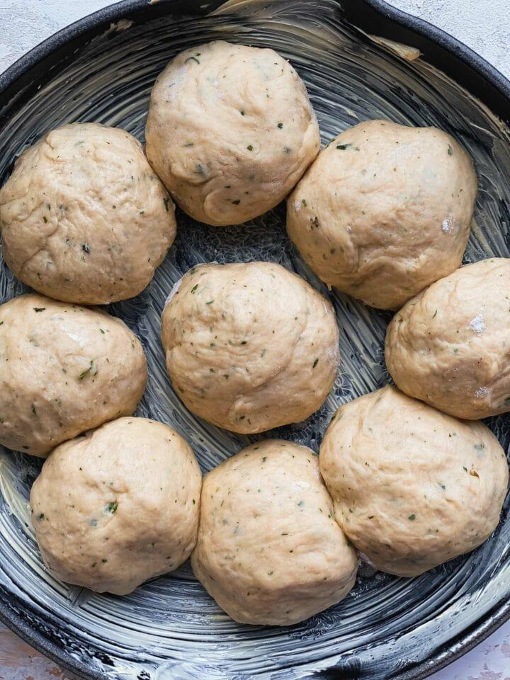Bread rolls in a skillet before baking