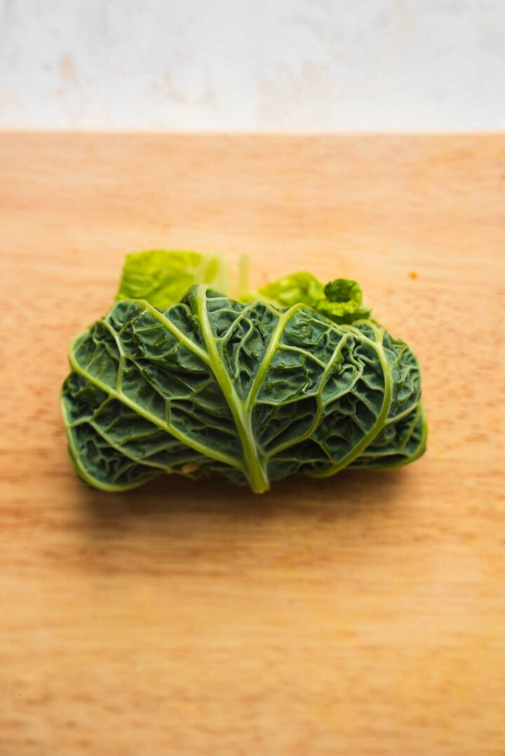 Rolled up cabbage leaf on a wooden board