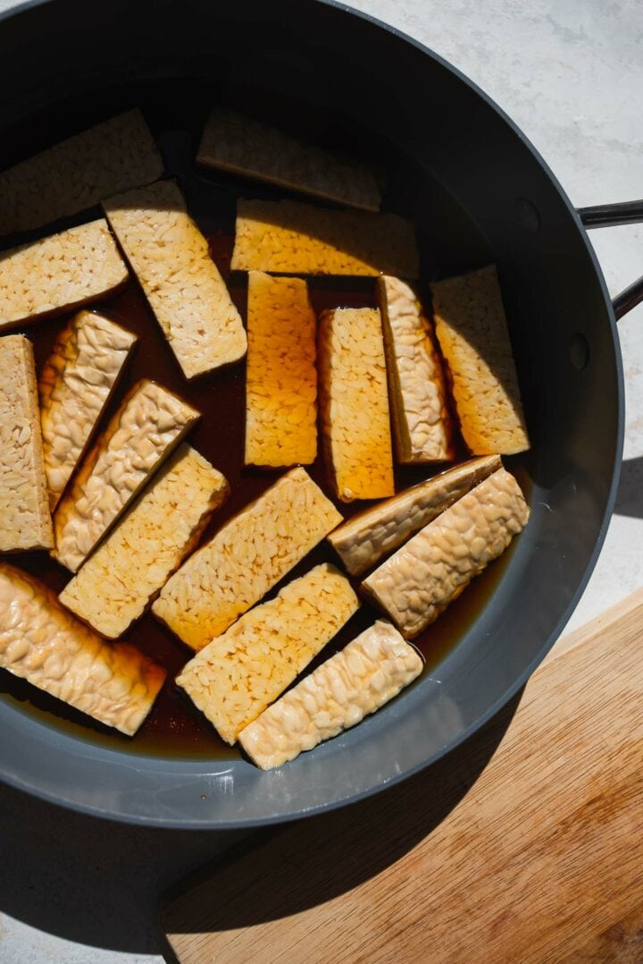 Tempeh being steamed in a frying pan