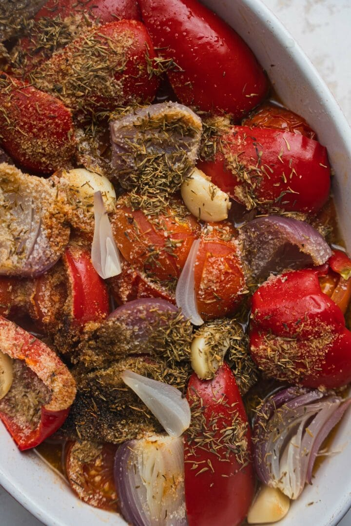Tomatoes, onions and peppers in a baking dish
