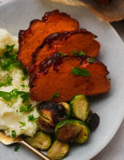 Vegan ham on a plate with mashed potatoes and Brussels sprouts
